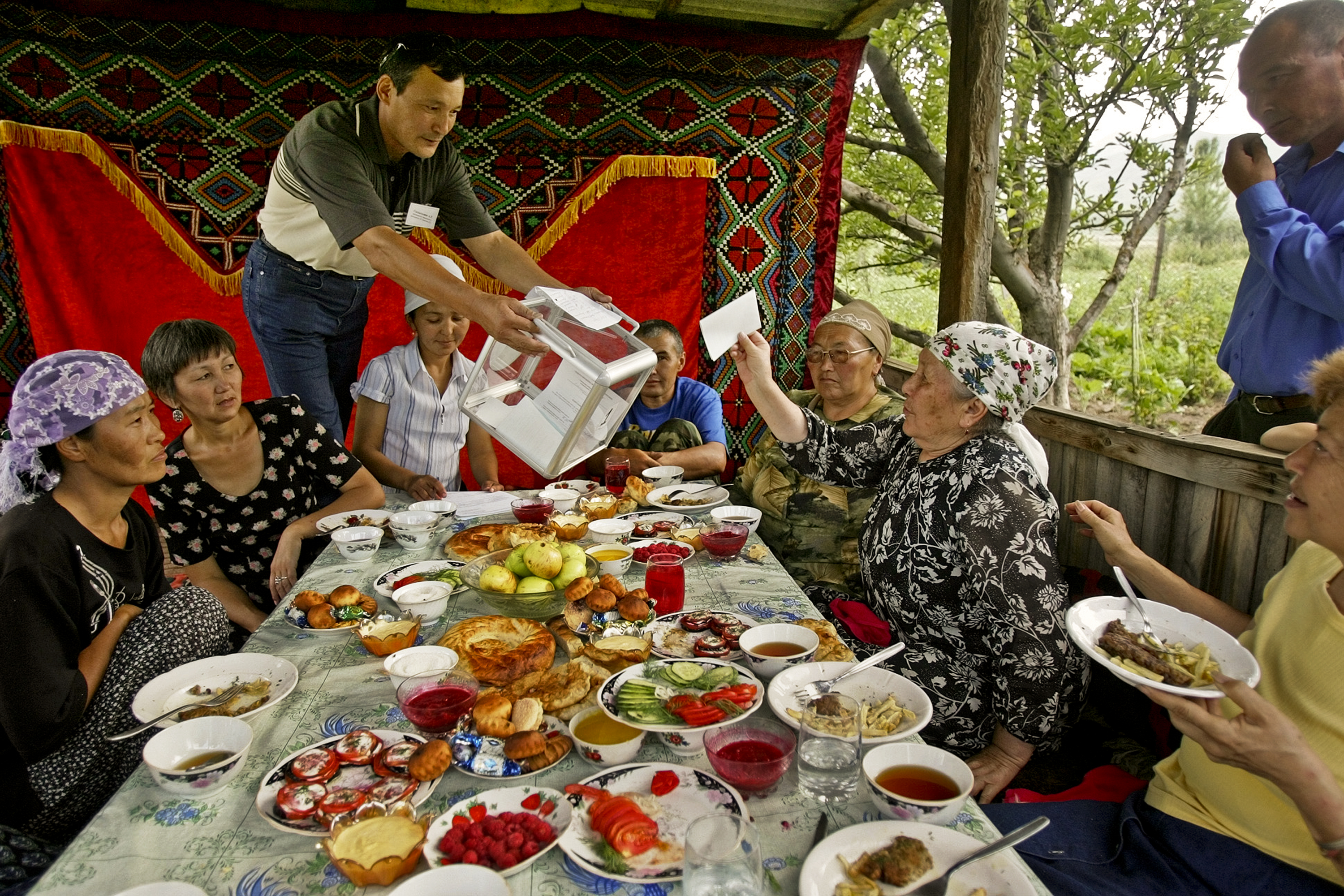 In Kyrgyzstan, Toktobubu Jantaliyeva (third from right) casts a presidential ballot as she and her relatives have lunch in their country house in the village of Gornaya, 2005.