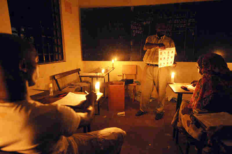 In Comoros, electoral agents count ballots by candlelight after the nation voted to replace their incumbent president, 2010.