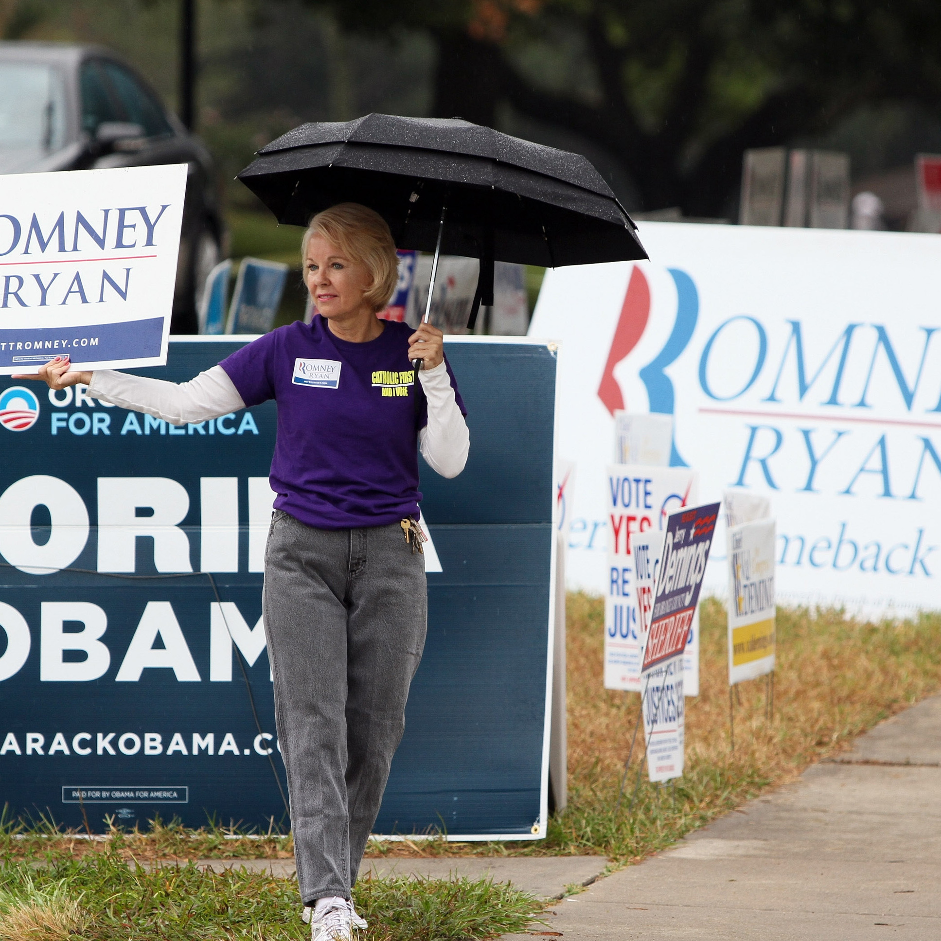 Elizabeth Doran holds a sign supporting Mitt Romney and Paul Ryan outside Precinct 116, at the Southwest Branch of the Orange County Library in south Orlando, Fla., on Tuesday.