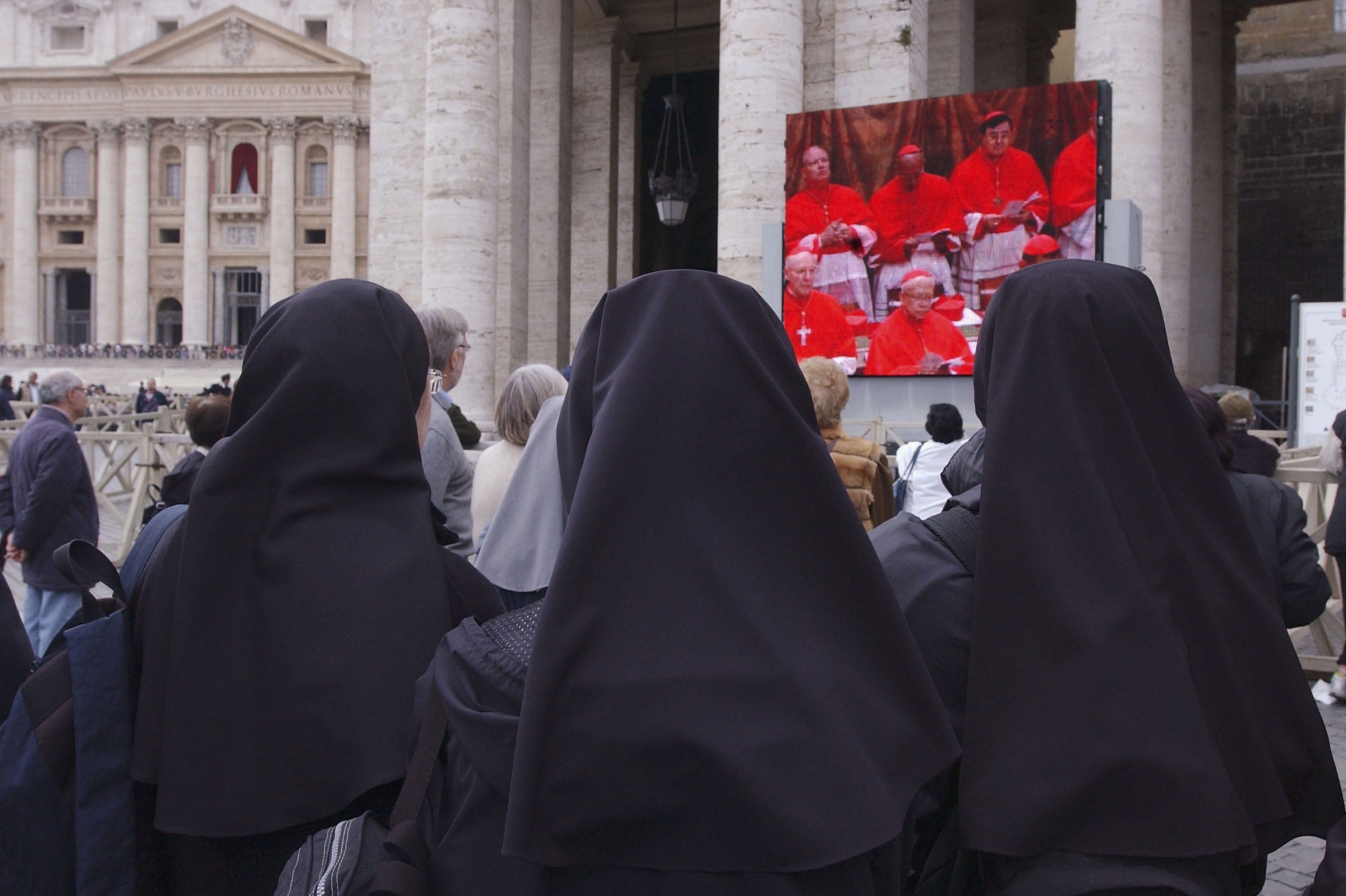 Nuns outside the Vatican watch a telecast of cardinals deliberating at the Papal Conclave to elect a new pope in 2005. The government of Vatican City, an ecclesiastical state, is overseen by the pope of the Roman Catholic church, who can only be elected by male cardinals.