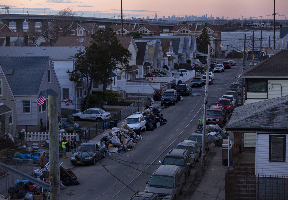 Debris lay in front of homes in a Rockaway neighborhood of the borough of Queens, New York, on Monday. The Manhattan skyline is seen in the background. (AP Photo/Craig Ruttle)