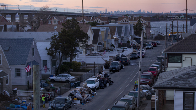 Debris lay in front of homes in a Rockaway neighborhood of the borough of Queens, New York, on Monday. The Manhattan skyline is seen in the background. (AP Photo/Craig Ruttle) (AP)