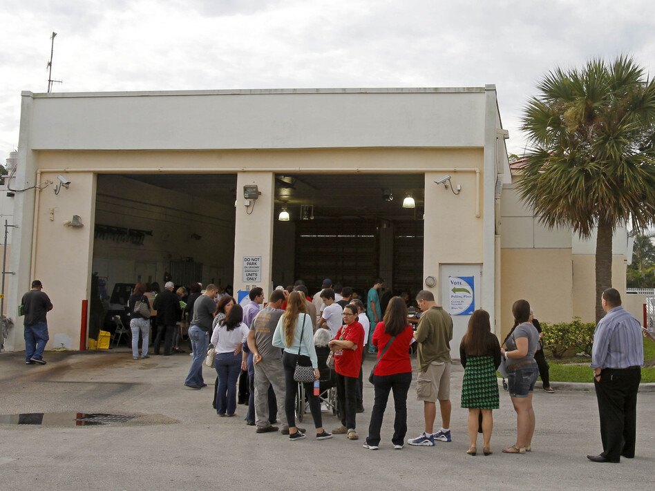 Voters stand in line as they prepare to cast their votes in Hialeah, Fla., on Tuesday.