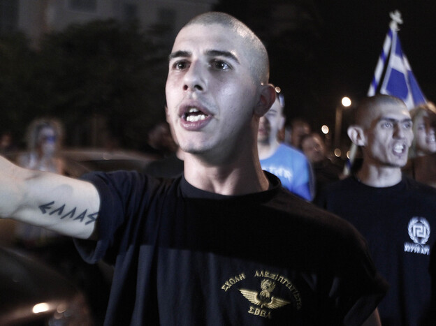 """Supporters of Golden Dawn celebrate the results of the elections outside of their Thessaloniki headquarters in June. The tattoo reads """"Greece."""""""
