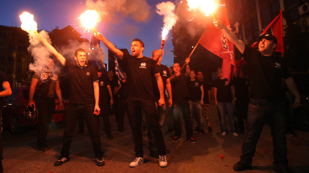 Members of the Greek ultranationalist Golden Dawn Party, sing the national anthem outside the party's office in Thessaloniki in June. The party's support has been boosted by anti-immigrant anger. (AFP/Getty Images)