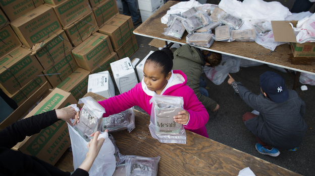 A young woman helps bag ready-to-eat meals for distribution to the residents of the Lower East Side who remain without power due to Superstorm Sandy on Friday. (AP)