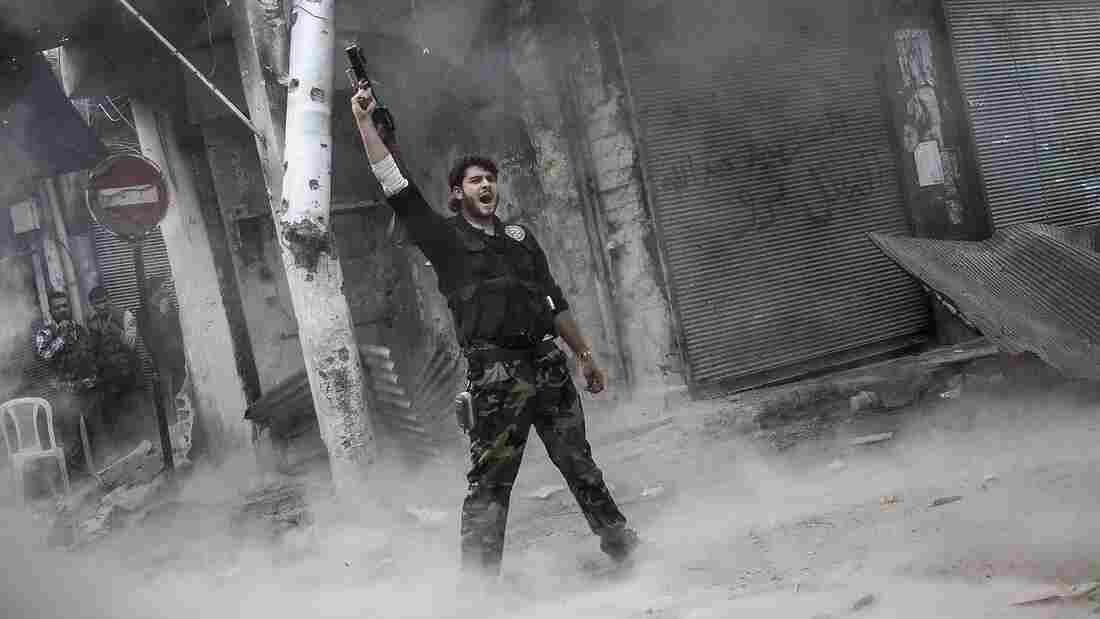 A rebel fighter raises his weapon after firing a missile Sunday toward Syrian government troops in the northern city of Aleppo. Syria's largest city has been the scene of heavy fighting for the past three months. Both sides control part of the city, and the fight has been a stalemate recently.
