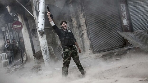 A rebel fighter raises his weapon after firing a missile Sunday toward Syrian government troops in the northern city of Aleppo. Syria's largest city has been the scene of heavy fighting for the past three months. Both sides control part of the city, and the fight has been a stalemate recently. (AP)