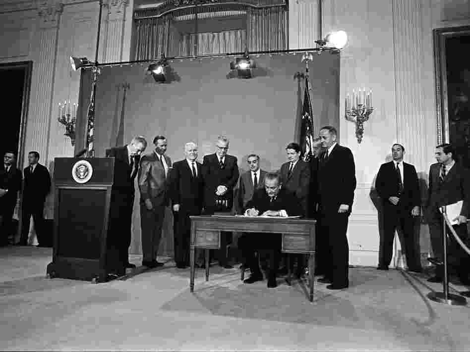 President Lyndon B. Johnson signs the Public Broadcasting Act of 1967, in the East Room of the White House.