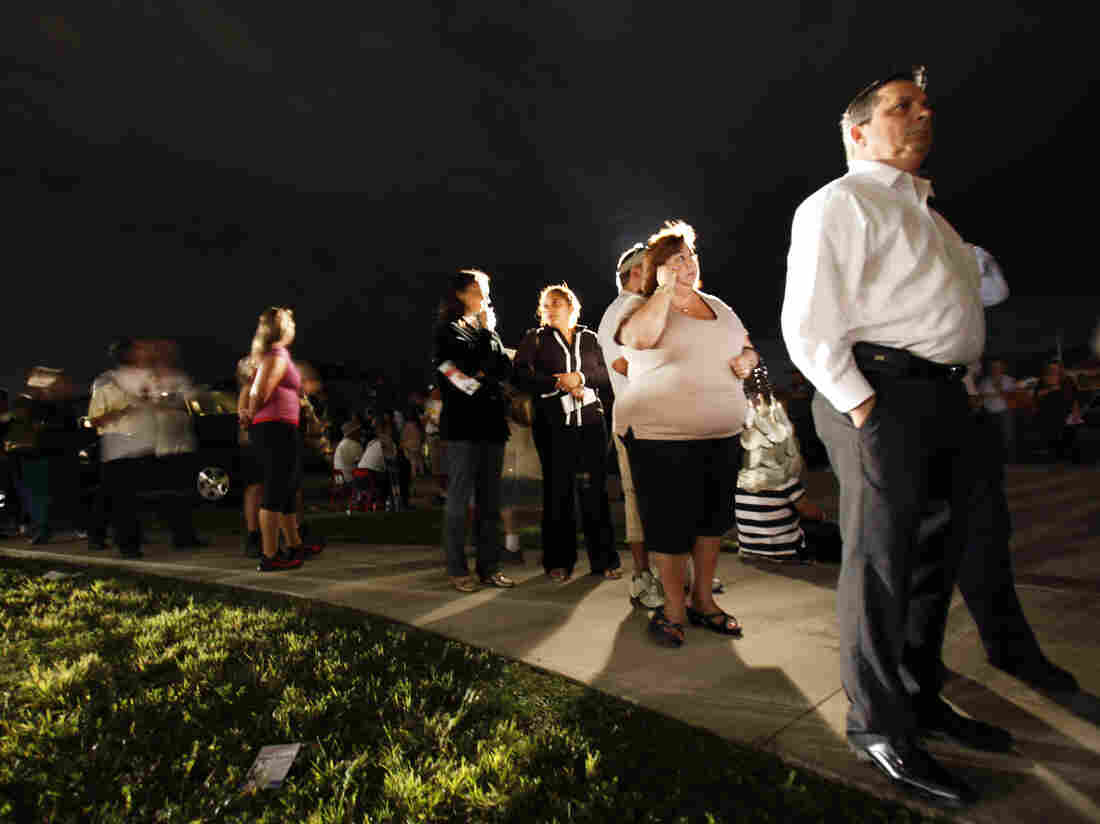 """Voters line up in the dark Tuesday to cast their ballots at a polling station in Miami. President Obama said the long lines nationwide were something """"we have to fix."""""""