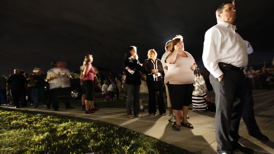 "Voters line up in the dark Tuesday to cast their ballots at a polling station in Miami. President Obama said the long lines nationwide were something ""we have to fix."" (AP)"