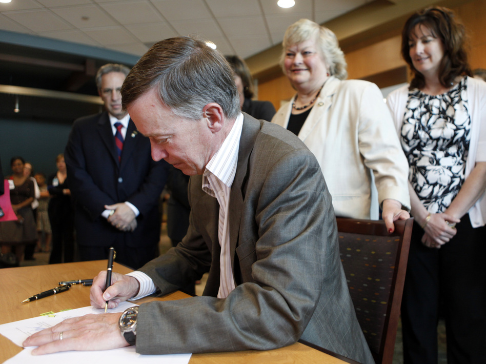 Colorado Gov. John Hickenlooper signs a bill in June 2011 to pave the way for a health insurance exchange in the state. (AP)