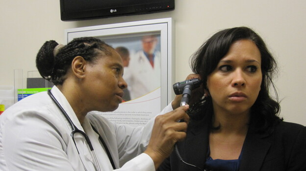 Dr. Wanda Simmons-Clemmons examines Dawn Antonelli at the PromptCare urgent care clinic. (Jenny Gold for NPR)