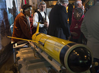 John Disney (second from left) looks over the underwater probe used in his company's ocean fertilization project, at a news conference in Vancouver, British Columbia, in October.