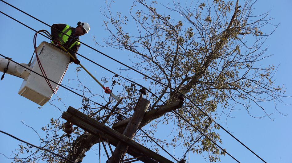 Crews work to restore power in Bethpage, N.Y., on Saturday. As of Wednesday, more than 200,000 Long Island residents were still without power, as a nor'easter made new outages likely. (Getty Images)