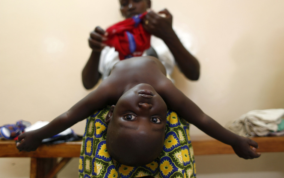 A mother dresses her baby after doctors examined him during the malaria vaccine trial at the Walter Reed Project Research Center in Kombewa in Western Kenya in October 2009.