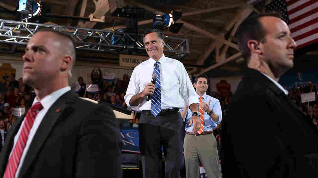 Before the vote, GOP nominee Mitt Romney and his running mate (Rep. Paul Ryan, in the background) were guarded by watchful Secret Service agents. After results came in, the agents quickly disappeared.