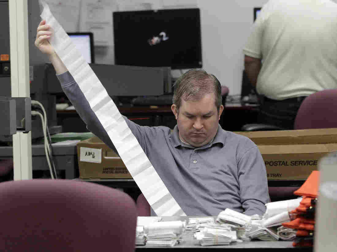 A Miami-Dade Elections Department employee tallies absentee ballot reports in Doral, Fla., on Thursday.