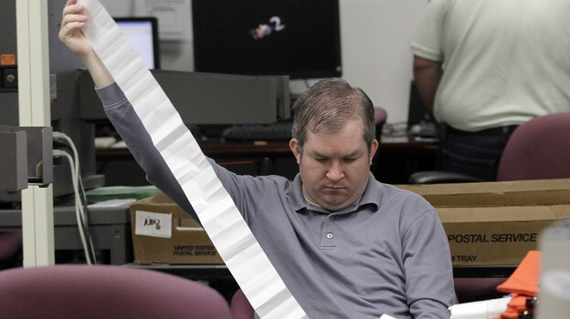 A Miami-Dade Elections Department employee tallies absentee ballot reports in Doral, Fla., on Thursday. (AP)