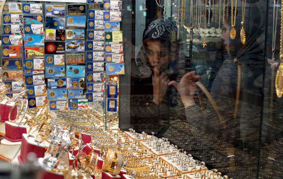 Iranian women look at a jewelry shop display in Tehran, Iran, in 2010. Iran now appears to be stockpiling gold in an attempt to stabili