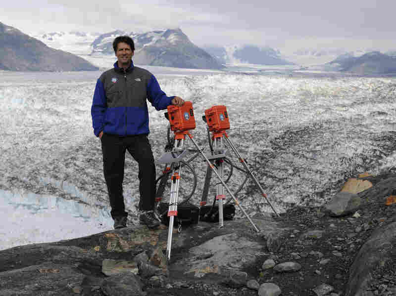 James Balog poses on the Columbia Glacier in Alaska with two EIS time-lapse cameras in 2009.