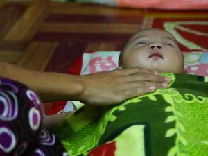 A mother comforts her sick child at the Whampa malaria clinic on the Thailand-Burma border. Children under 5 years of age are especially vulnerable to the disease.
