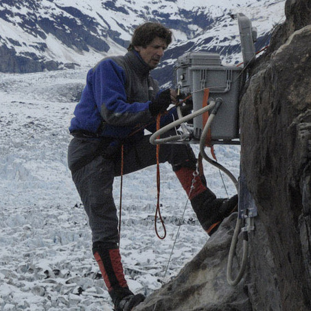 James Balog hangs off a cliff on the Columbia Glacier in Alaska to install a time-lapse camera.