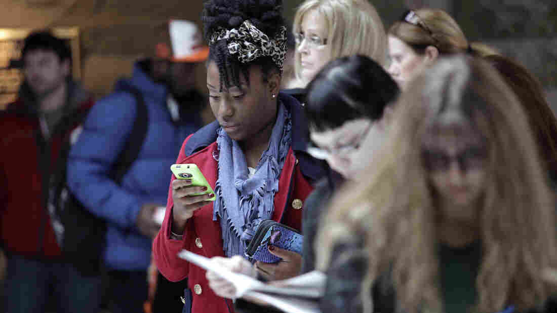 Elizabeth Ball checks her phone while waiting to vote Monday in Bowling Green, Ohio.