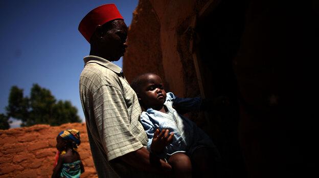 Ado Ibrahim carries his son Aminu through a village in northern Nigeria. Aminu, 4, was par