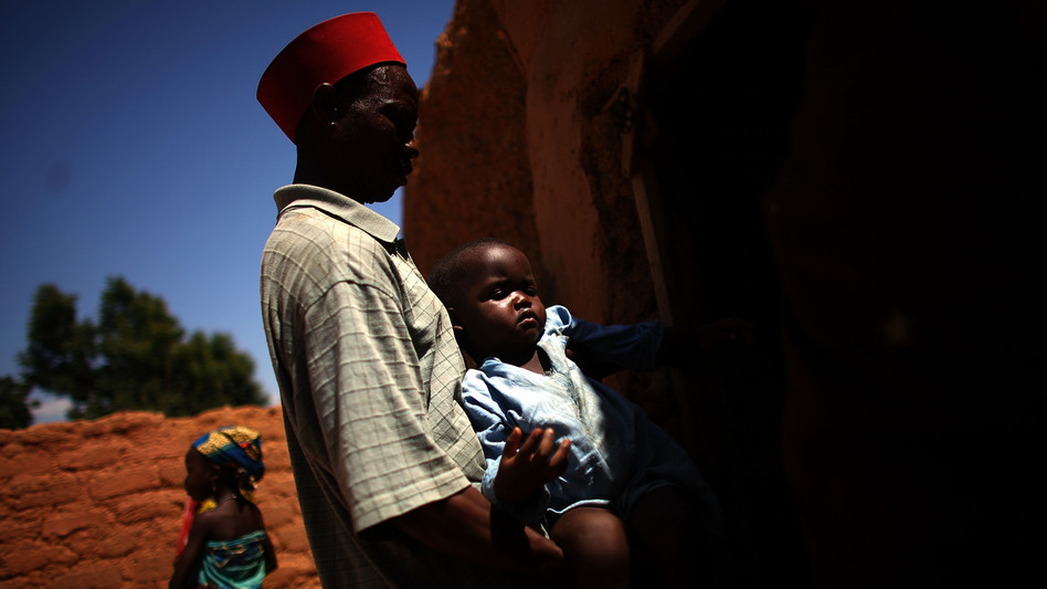 Ado Ibrahim carries his son Aminu through a village in northern Nigeria. Aminu, 4, was paralyzed by polio in August.