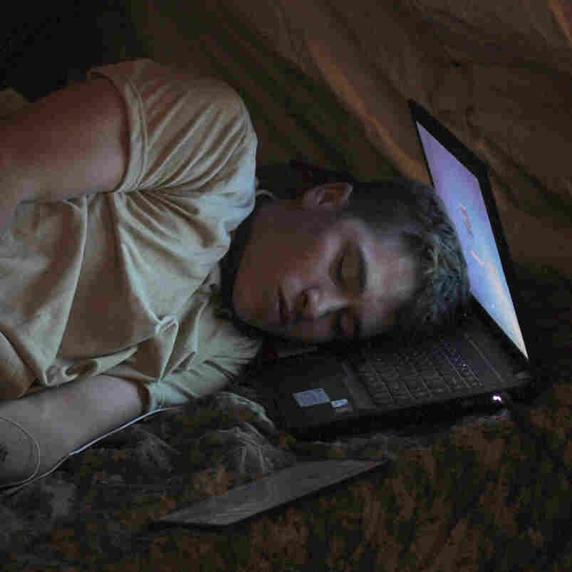 U.S. Army Pvt. Freymond Tyler sleeps on a laptop next to his gun at combat outpost Makuan in Kandahar province, Afghanistan, in 2011.