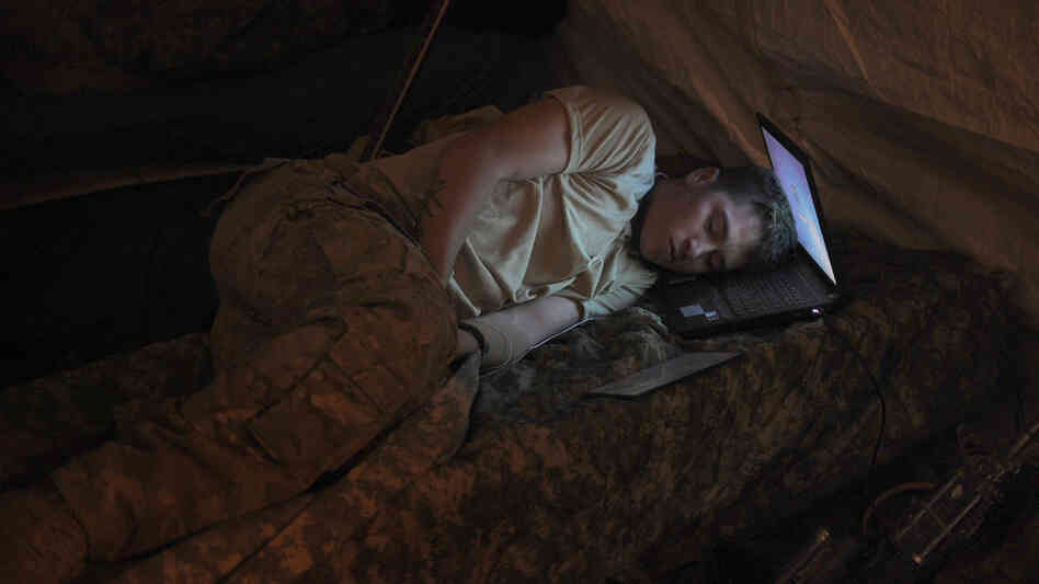 U.S. Army Pvt. Freymond Tyler sleeps on a laptop next to his gun at combat outpost Makuan in Kanda