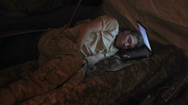 U.S. Army Pvt. Freymond Tyler sleeps on a laptop next to his gun at combat outpost Makuan in Kandahar province, Afghanistan, in 2011. (AFP/Getty Images)