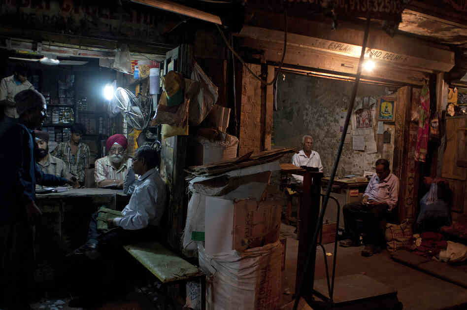 Indian workers at a spare parts store discuss business as the proprietor of a neighboring business sits in