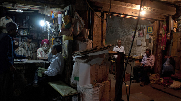Indian workers at a spare parts store discuss business as the proprietor of a neighboring business sits in his shop in New Delhi. (AFP/Getty Images)