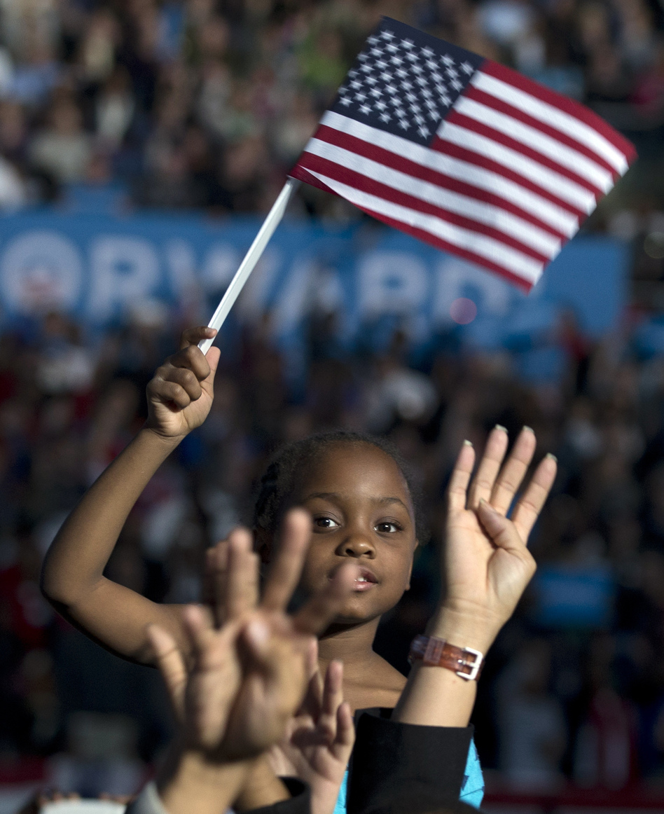 "Amara Hayles, 6, sits atop her dad's shoulders as the crowd shouts ""four more years"" during a speech by President Obama Nov. 5 in Columbus, Ohio. (AP)"