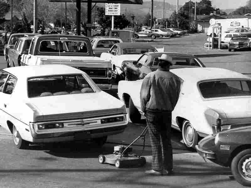 Drivers and a man pushing a lawnmower line up at gas station in San Jose, Calif., on March 15, 1974.