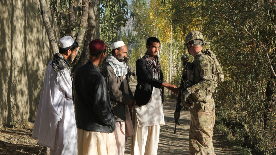 U.S. troops from the 1-91 Cavalry question Afghan civilians in Baraki Barak district in Logar Province, south of Kabul. (NPR)