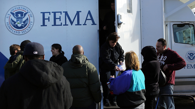 Residents wait for information from FEMA in the Rockaway neighborhood of Queens, N.Y. Superstorm Sandy washed away a large section of the iconic boardwalk here on Nov. 2. (Getty Images)