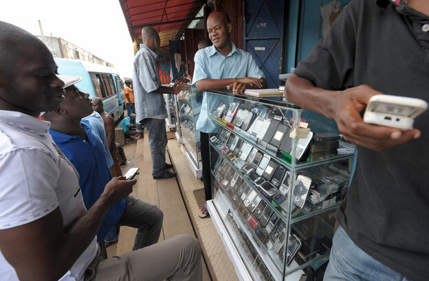 Men look at mobile phones at the Adjame market in Abidjan, Ivory Coast. The market for mobile telephones in developing countries has grown quickly, and now Facebook and Google are trying to get users to use the Internet on their devices.