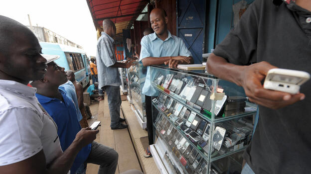 Men look at mobile phones at the Adjame market in Abidjan, Ivory Coast. The market for mobile telephones in developing countries has grown quickly, and now Facebook and Google are trying to get users to use the Internet on their devices. (AFP/Getty Images)
