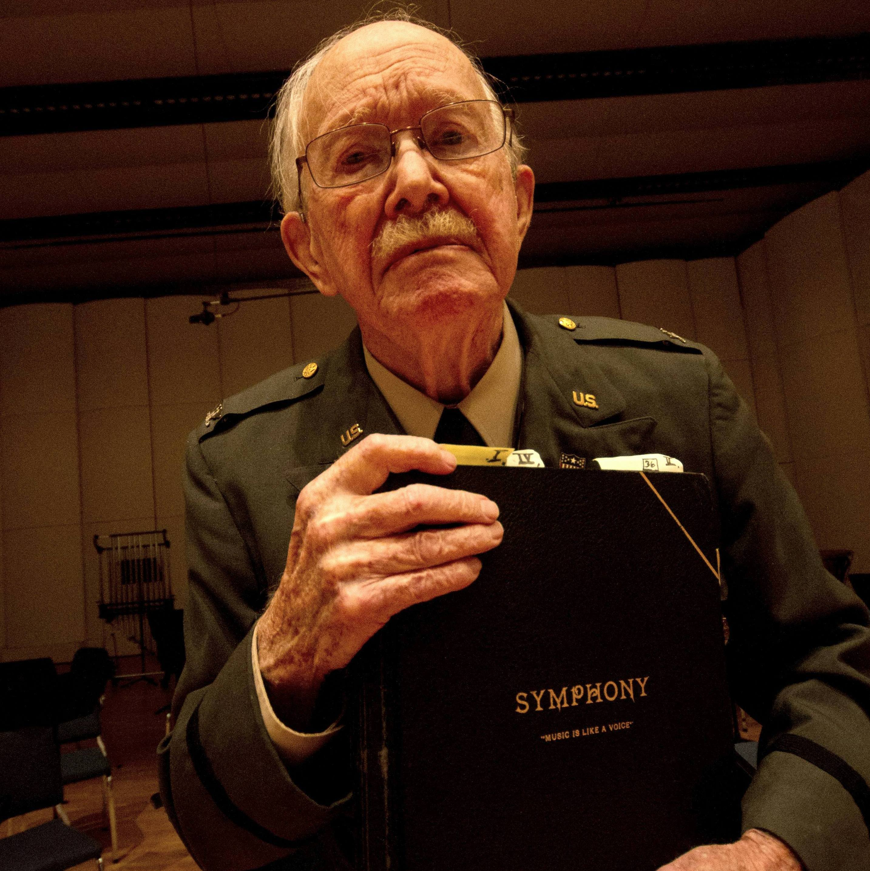 Harold Van Heuvelen stands with the symphony score he'd composed seven decades earlier.