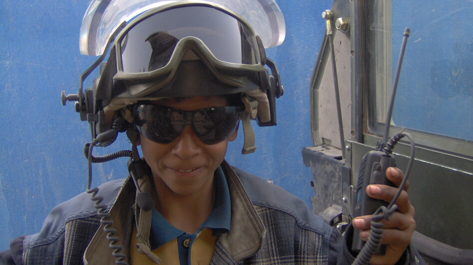 Ali, an Iraqi teenager, wears Spc. Justin Cliburn's helmet and radio equipment in Baghdad. Ali and Cliburn became unlikely friends while Cliburn trained Iraqi police in 2005 and 2006. (Courtesy of Justin Cliburn)