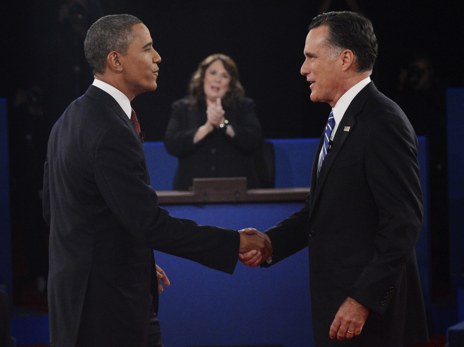 Moderator Candy Crowley applauds as President Obama shakes hands with former Massachusetts Gov. Mitt Romney during the second presidential debate on Oct. 16.