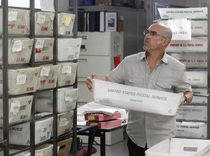 A worker prepares boxes of absentee ballots to be scanned at the Miami-Dade County Elections Department on Tuesday.