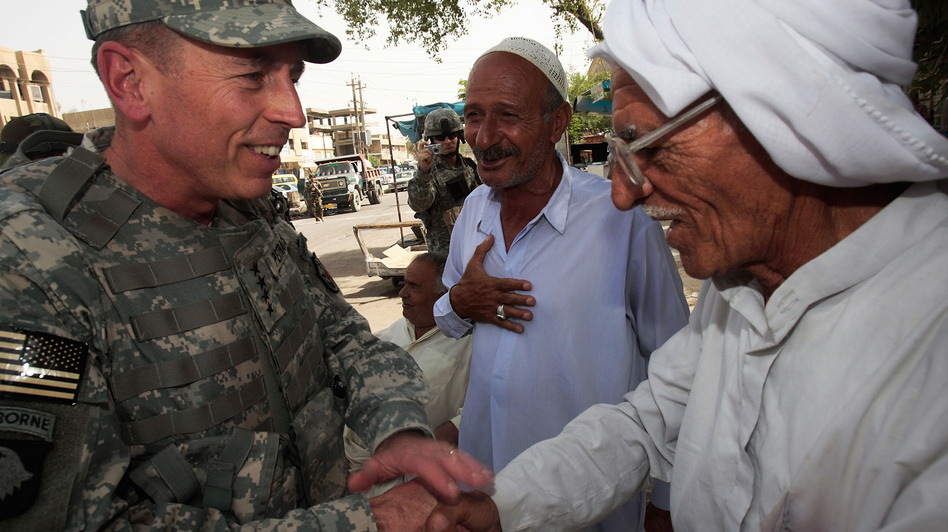 Gen. David Petraeus greets an Iraqi man at a tea shop in Baghdad in 2007. In 2011, Petraeus left the Army to become CIA director. He resigned Friday, citing an extramarital affair. (Getty Images)