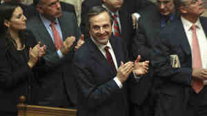 Greek Prime Minister Antonis Samaras and lawmakers from his New Democracy applaud after voting o