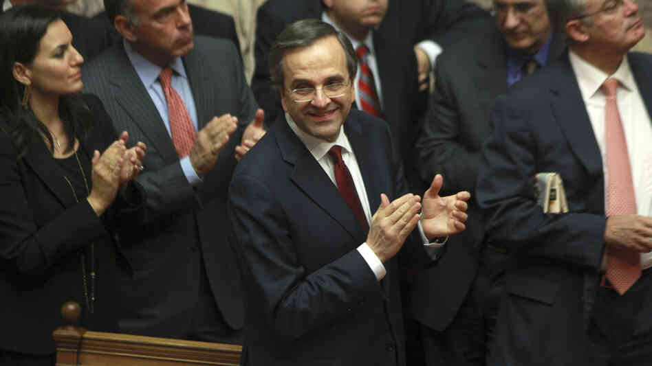 Greek Prime Minister Antonis Samaras and lawmakers from his New Democracy applaud after voting on th