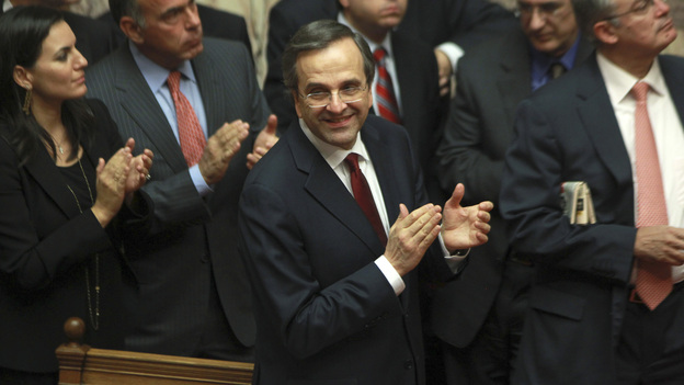 Greek Prime Minister Antonis Samaras and lawmakers from his New Democracy applaud after voting on the country's 2013 budget in Athens early Monday. Greek lawmakers approved the country's 2013 austerity budget, an essential step in Greece's efforts to persuade its international creditors to unblock a vital rescue loan installment without which the country will go bankrupt. (AP)