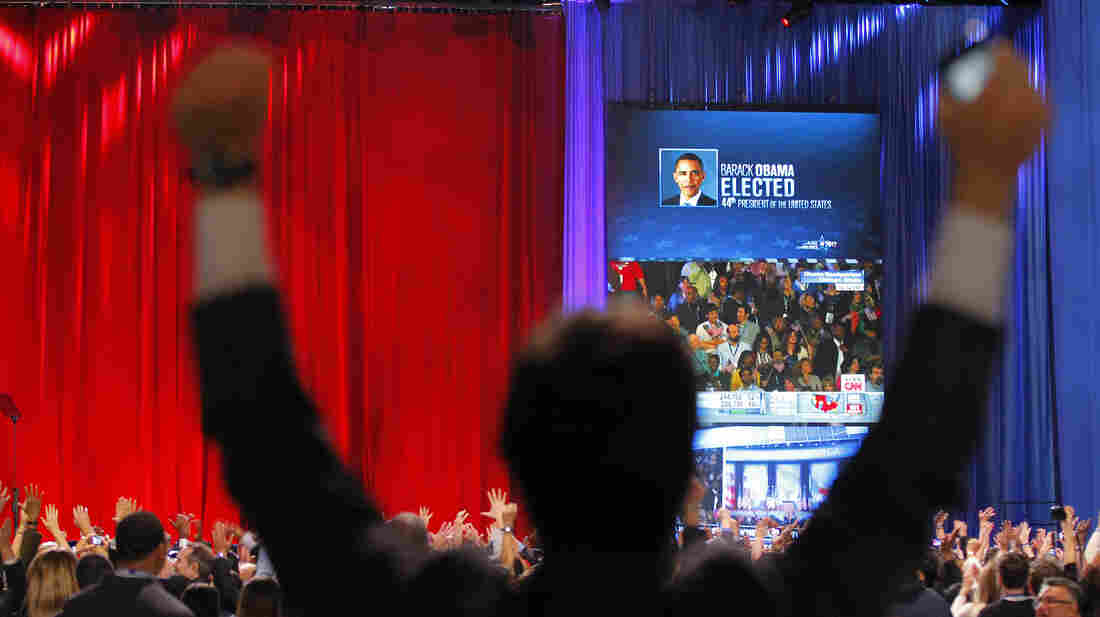 A supporter of President Barack Obama raises his arms as it is announced that Obama was re-elected during an election night watch party in Chicago.
